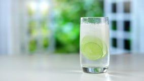 涌入与冰、柠檬和石灰的一块玻璃的一份刷新的饮料 股票视频
