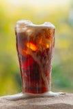 涌入与冰块的玻璃的可乐水在沙子 库存照片