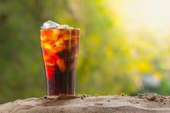 涌入与冰块的玻璃的可乐水在沙子 图库摄影