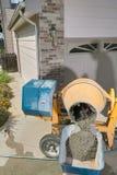 涌入独轮车的黄色水泥搅拌车 库存照片