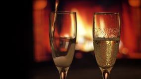 涌入香槟与与火焰的舒适温暖的壁炉的两块空的玻璃特写镜头射击在背景 股票录像