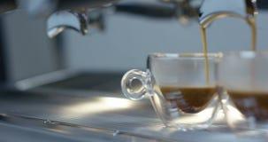 涌入从咖啡机器的一个两个透明杯子的热的浓咖啡咖啡滑子在4k 股票录像