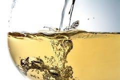 涌入玻璃特写镜头,酒,飞溅,泡影,嘶嘶响的酒小河  库存图片
