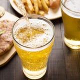 涌入玻璃的啤酒用牛排和炸薯条在木头 免版税图库摄影