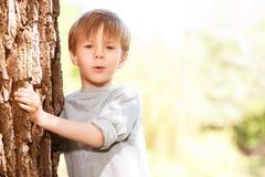 涌现从后面树的小男孩 免版税库存照片