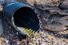 涌现从地面的黑塑料管子 免版税库存照片