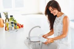 洗涤一个杯子的妇女在白色厨房里 在backgrou的菜 免版税图库摄影