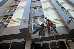 洗涤一个现代大厦的门面的工业登山人 库存图片