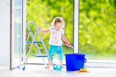 洗涤一个窗口的俏丽的女孩在绝尘室 库存照片