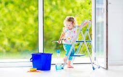 洗涤一个窗口的迷人的女孩在绝尘室 免版税图库摄影