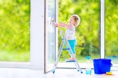 洗涤一个窗口的逗人喜爱的卷曲女孩在绝尘室 免版税库存图片