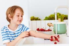 洗涤一抱甜樱桃的逗人喜爱的年轻男孩在自来水下在厨房里 库存图片