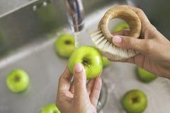 洗涤与竹刷子的年轻素食主义者女孩绿色苹果 拿着新鲜水果的手在厨房水槽的自来水下 免版税库存照片