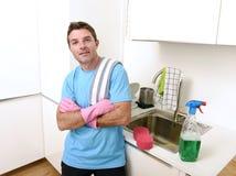 洗涤与洗涤剂浪花瓶和海绵佩带的手套的年轻可爱和愉快的人 免版税图库摄影