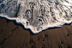 洗涤含沙岸的波浪 免版税库存照片