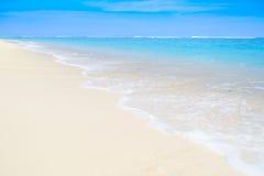 洗涤在含沙海滨的波浪 免版税库存图片