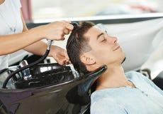 洗涤在理发沙龙的人头发 免版税库存照片