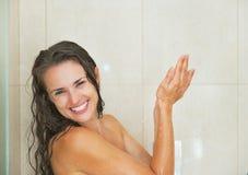 洗涤在阵雨的微笑的少妇 免版税库存图片