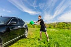 洗涤在绿色领域的人黑汽车 图库摄影