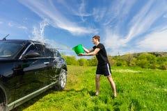 洗涤在绿色领域的人黑汽车 库存图片