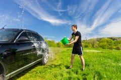 洗涤在绿色领域的人黑汽车 免版税库存照片