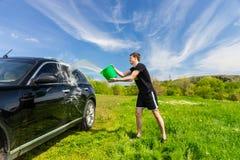 洗涤在绿色领域的人黑汽车 库存照片