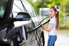 洗涤在洗车的可爱的小女孩一辆汽车 免版税库存照片