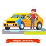 洗涤她的有喷洒的水管的妇女家用汽车 免版税库存图片