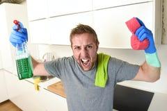年轻洗涤家庭厨房干净恼怒在重音的人拿着清洁洗涤剂浪花的和海绵 库存照片