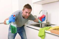 年轻洗涤家庭厨房干净恼怒在重音的人拿着清洁洗涤剂浪花的和海绵 免版税库存照片