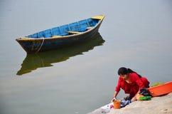 洗涤布料的尼泊尔妇女在Phewa湖 免版税库存图片