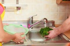 洗涤新鲜蔬菜的夫妇在厨房里 免版税库存图片