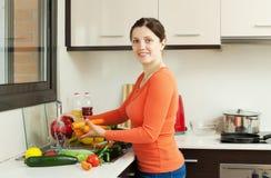 洗涤新鲜蔬菜的微笑的俏丽的妇女 库存照片