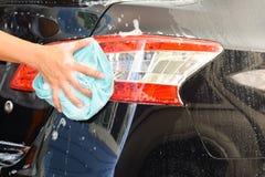 洗涤有布料的人的手一辆肥皂的黑汽车 库存图片