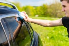 洗涤有肥皂的海绵的人黑汽车 库存照片