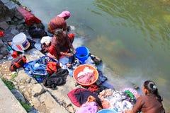洗涤沿河的尼泊尔妇女衣裳 免版税库存照片