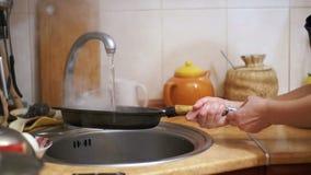洗涤热的煎锅把冷水变成喷气机在家庭厨房水槽的蒸汽  慢的行动 股票视频