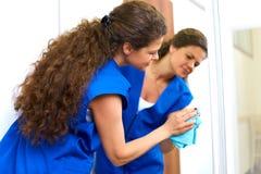 洗涤窗口的可爱的妇女 Cleaning Company工作者wor 免版税图库摄影