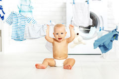 洗涤衣裳和笑的乐趣愉快的男婴在洗衣店 库存照片