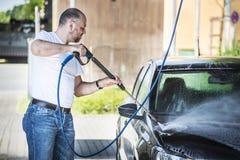 洗涤他的汽车的人 免版税库存照片