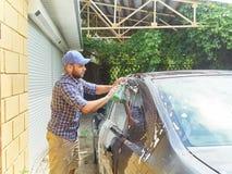 洗涤他的黑汽车的人在房子附近 免版税库存图片