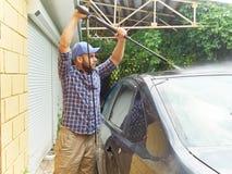 洗涤他的黑汽车的人在房子附近 免版税图库摄影