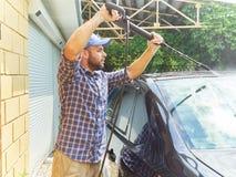 洗涤他的黑汽车的人在房子附近 库存照片