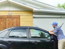 洗涤他的黑汽车的人在房子附近 免版税库存照片