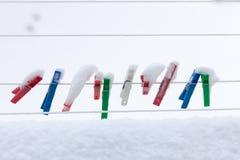 洗涤洗衣店的五颜六色的夹子报道了雪室外小条的绳索。冬天。 图库摄影