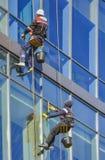 洗涤Windows的高空作业的建筑工人 免版税图库摄影