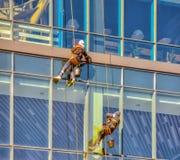 洗涤Windows的高空作业的建筑工人 库存图片