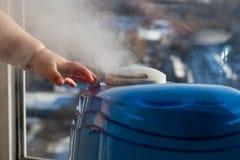 润湿器生产蒸气用婴孩` s手 免版税库存照片
