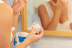 润湿奶油色在女性手上在卫生间里 免版税库存照片