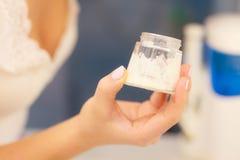 润湿奶油色在女性手上在卫生间里 图库摄影